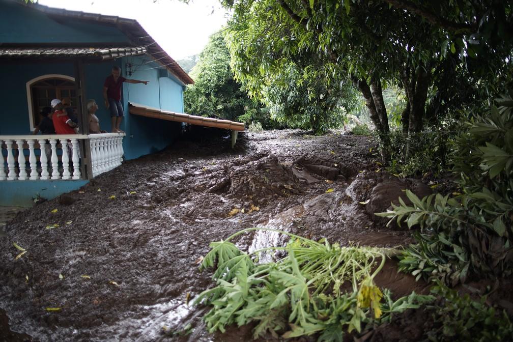Homem aponta para a lama que invadiu a casa da família em Brumadinho após rompimento da barragem da Vale. — Foto: Leo Correa/AP