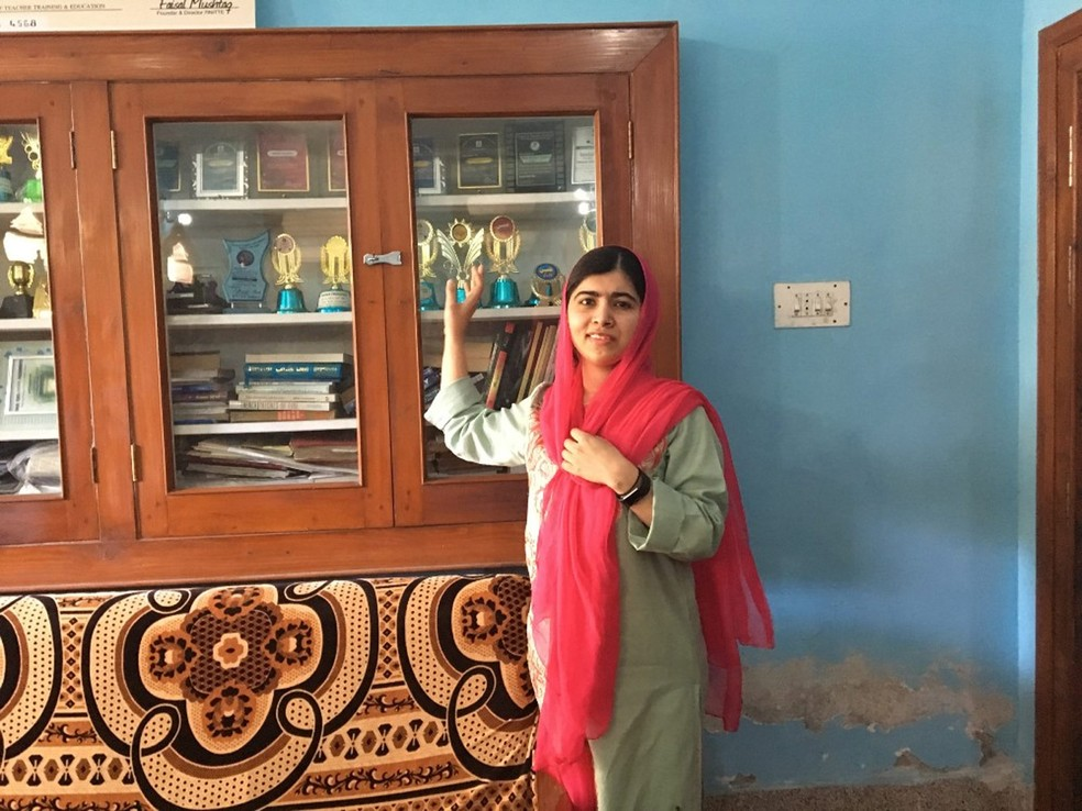 Malala posa em frente aos seus troféus escolares em seu antigo quarto no Vale do Swat, no Paquistão (Foto: Divulgação/Insiya Syed/Malala Fund)