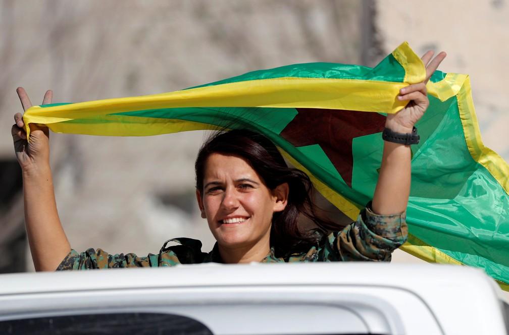 Mulher combatente das FDS comemora vitória contra jihadistas do Estado Islâmico em Raqqa (Foto: REUTERS/Erik De Castro)