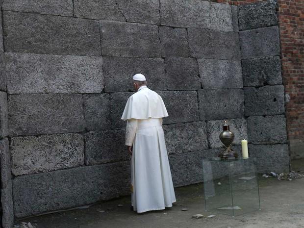 Papa Francisco reza diante da parede da morte, usada na execução de presos (Foto: David W Cerny / Reuters)
