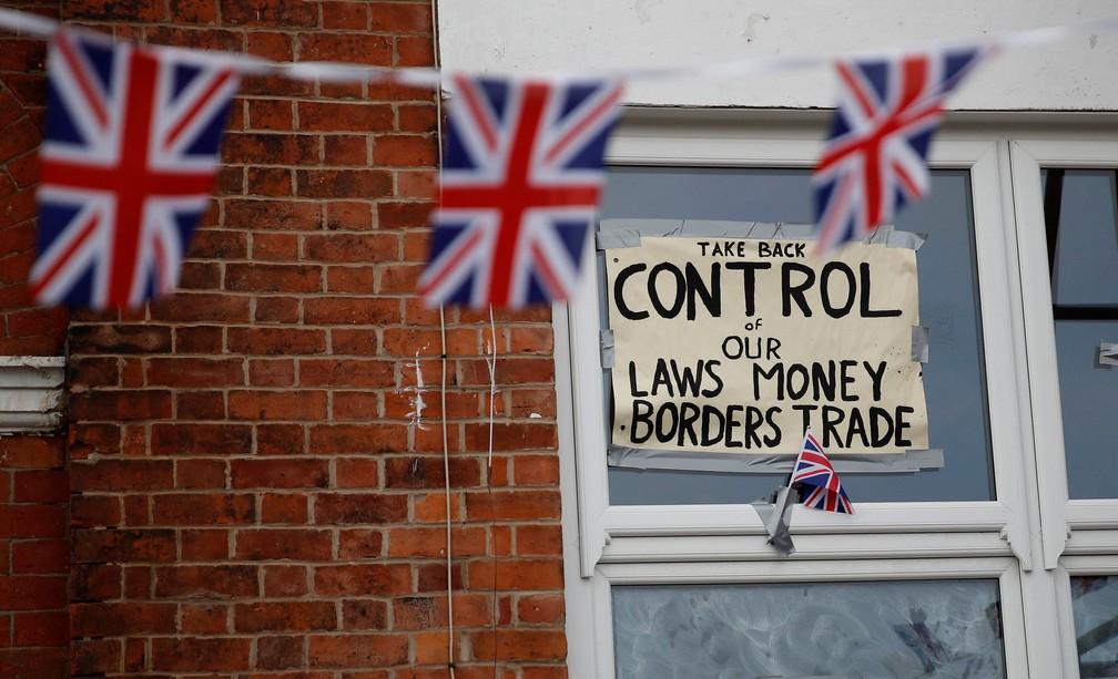 'Retome o controle de nossas leis monetárias e acordos de fronteira', diz cartaz fixado em janela de Altrinchan, no Reino Unido. Manifestantes pró-Brexit pedem saída da União Europeia sem acordo — Foto: Phil Noble/Reuters