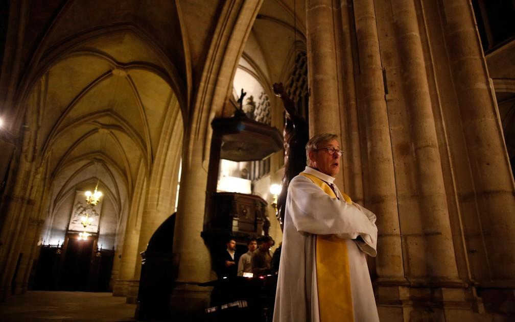 O reitor da Catedral de Notre-Dame, Patrick Chauvet, participa da missa de Natal na igreja de Saint-Germain l'Auxerrois, na terça-feira (24) — Foto: AP Photo/Thibault Camus