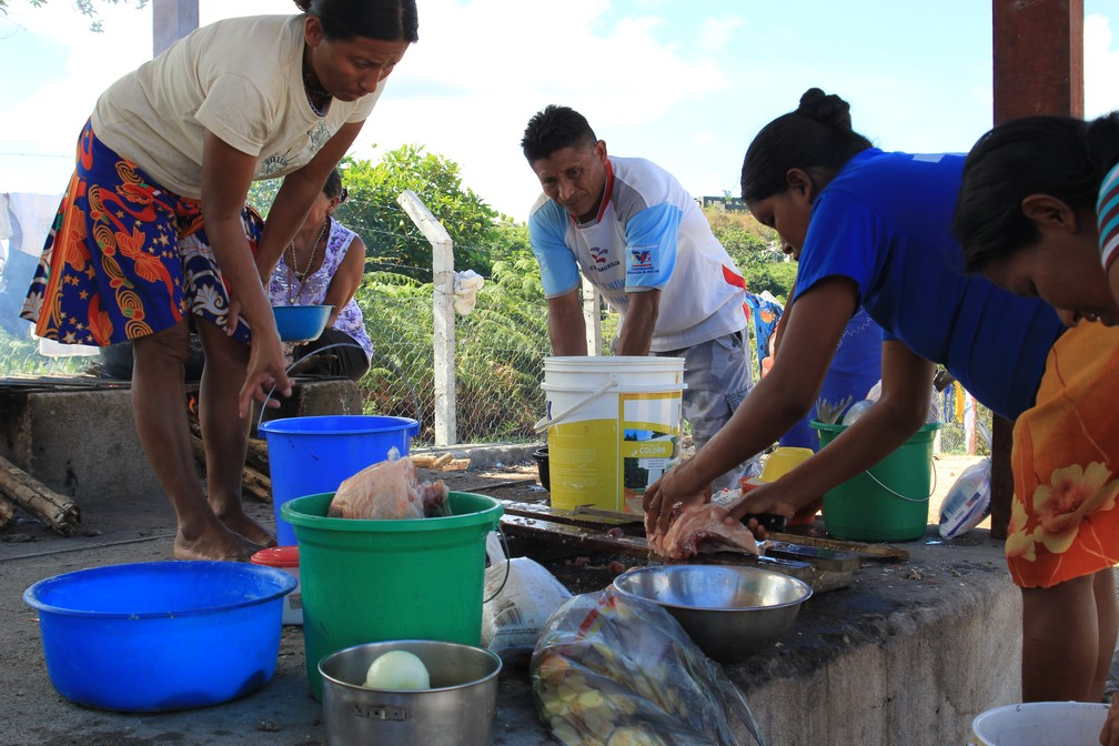 Índias cozinham do lado de fora do abrigo enquanto a cozinha coletiva não fica pronta (Foto: Emily Costa/G1 RR)
