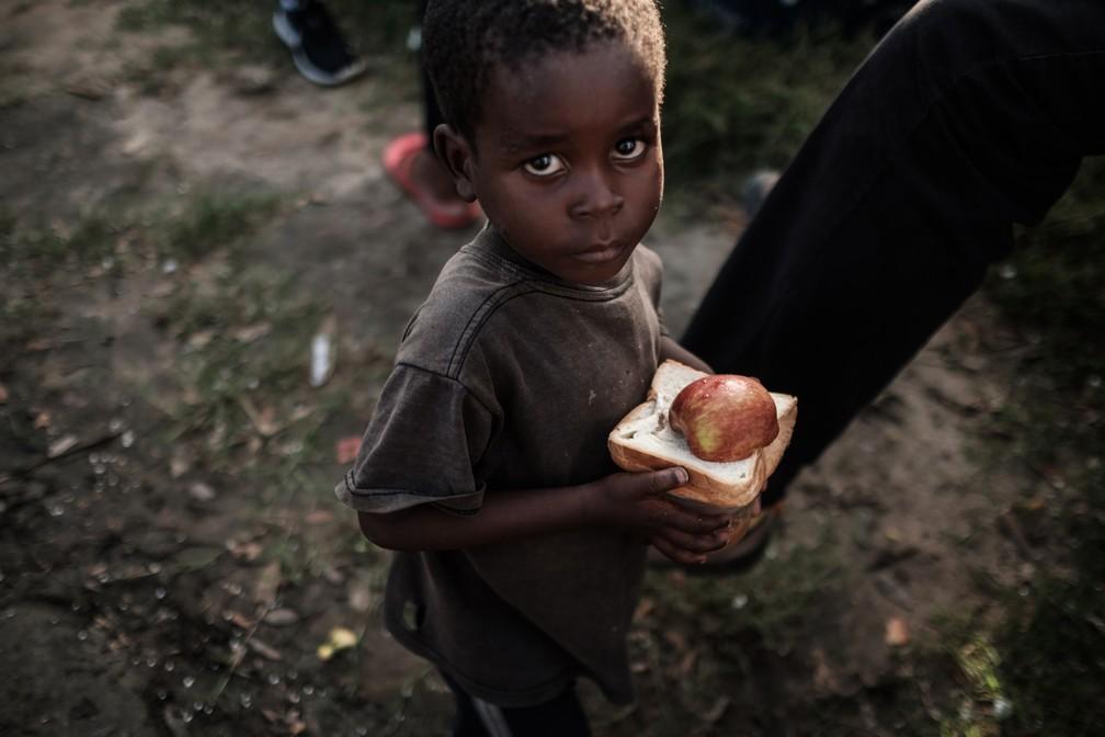 Menino recebe comida de um centro de distribuição de um supermercado em Dondo, a cerca de 35km de Beira, em Moçambique, nesta quarta (27). — Foto: Yasuyoshi Chiba/AFP
