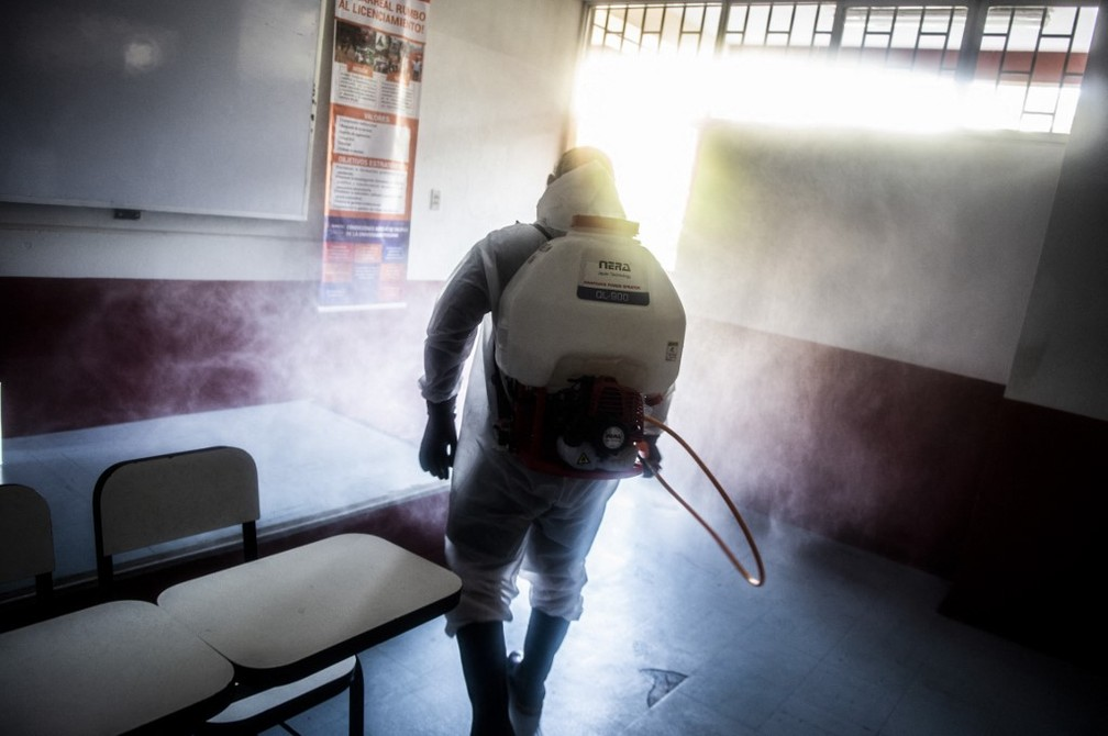 Agente higieniza escola em Lima neste sábado (10) para prepará-la para a eleição presidencial deste domingo — Foto: AFP/Ernesto Benavides