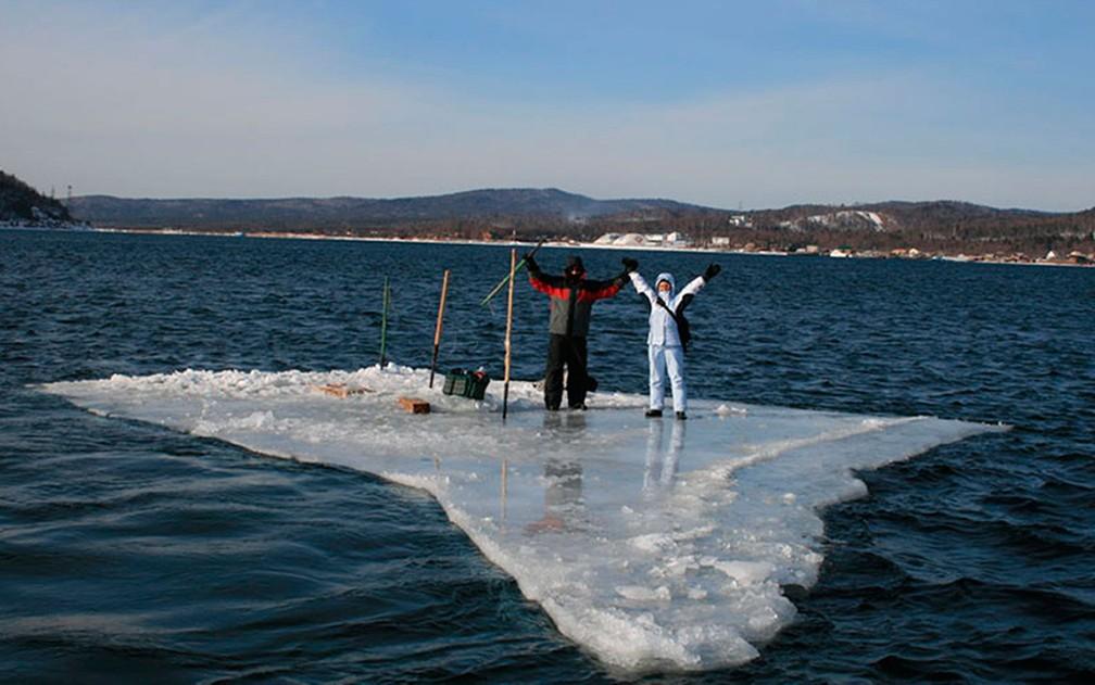 Dois pescadores usam bloco menor de gelo como balsa para tentar chegar à costa da ilha de Sakhalin, na Rússia, na terça-feira (28) — Foto: Russia Emergency Situations Ministry press service via AP