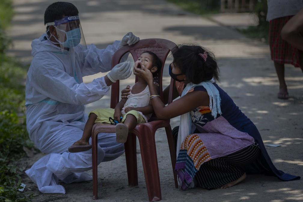Trabalhador de saúde indiano coleta swab nasal de criança para teste de Covid-19 na vila de Burha Mayong, distrito de Morigaon, estado de Assam, na Índia, em 22 de maio de 2021 — Foto: Anupam Nath/AP