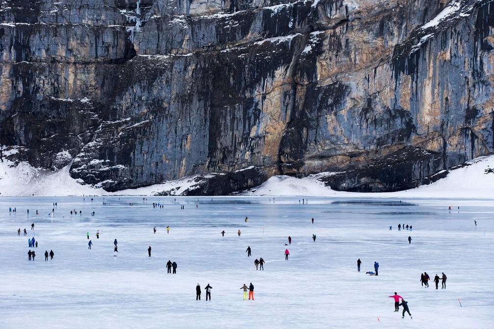 7 de janeiro - Pessoas esquiam no lago montanhoso congelado Oeschinensee, que fica a mais de 1.500 metros de altitude perto de Kandersteg, na Suíça (Foto: Peter Klaunzer/Keystone via AP)