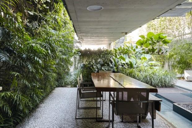 Jantar. A mesa foi colocada no jardim, em frente à cozinha. O muro lateral foi tomado por cissus-graúdo com grama-preta. Do outro lado, a canaleta de água se transforma em um espelho d'água. Atrás, pândano-rasteiro, filodendro-melinoni e barba-de-serpente (Foto: Victor Affaro / Editora Globo)