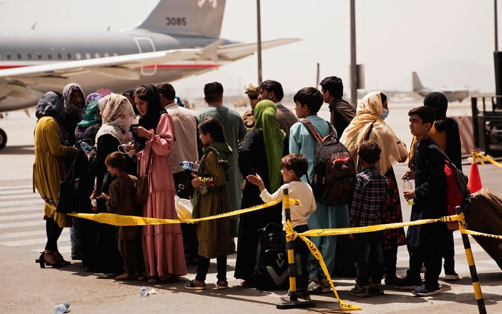 Civis afegãos se preparam para embarcar em avião para deixar o país no Aeroporto Internacional Hamid Karzai, em Cabul, na quarta-feira (18) — Foto: Staff Sgt. Victor Mancilla/U.S. Marine Corps via AP