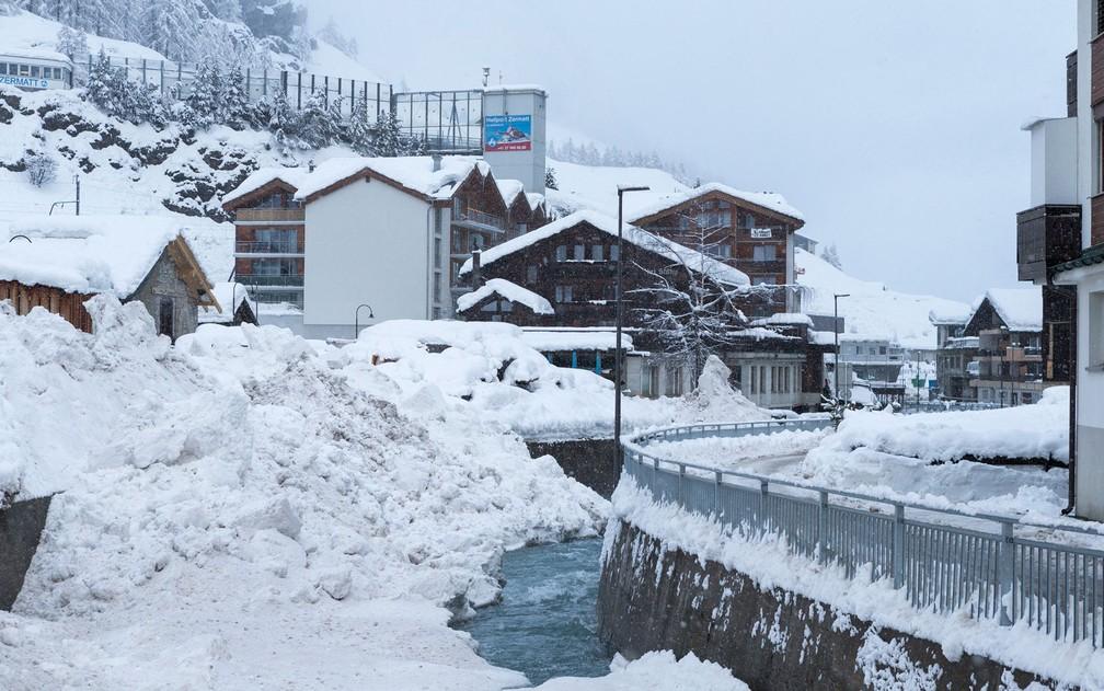 Neve é jogada em rio depois de ser removida da Estrada por caminhões, em Zermatt, na Suíça, na terça-feira (9) (Foto: Dominic Steinmann/Keystone via AP)