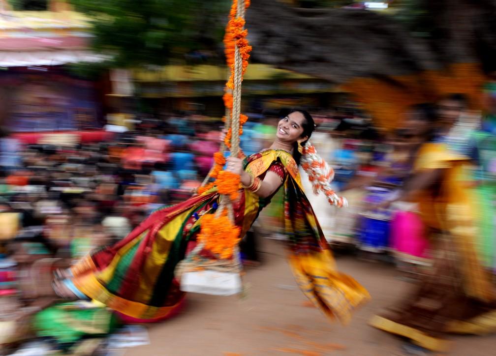 9 de janeiro - Uma estudante sorri em um balanço durante as celebrações do Pongal, o festival de colheita Tamil, em uma faculdade em Chennai, na Índia (Foto: Arun Sankar/AFP)