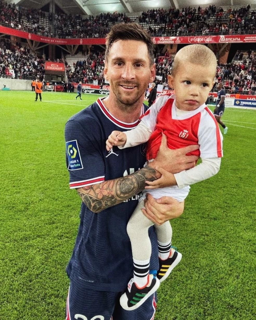 Messi com filho do goleiro do Reims após partida pelo Campeonato Francês — Foto: Predrag Rajkovic