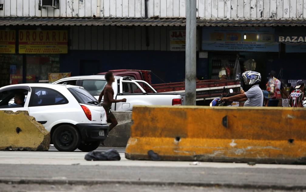 Homem corre entre os carros na Avenida Brasil (Foto: Marcos Serra Lima/G1)
