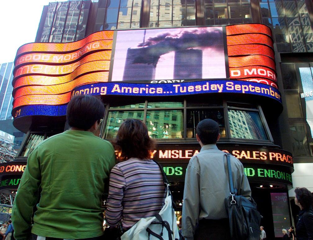 Pessoas assistem telão na Times Square, no Centro de Manhattan, mostrando o World Trade Center em chamas na parte sul da ilha antes de a segunda torre ser atingida — Foto: Shannon Stapleton/Reuters/Arquivo