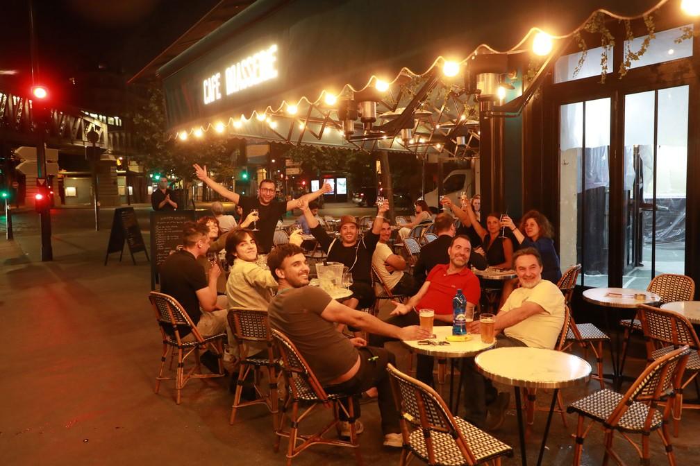 Parisienses voltam aos bares ainda na madrugada desta terça-feira (2). Estabelecimentos puderam reabrir à meia noite  — Foto: Ludovic Marin / AFP