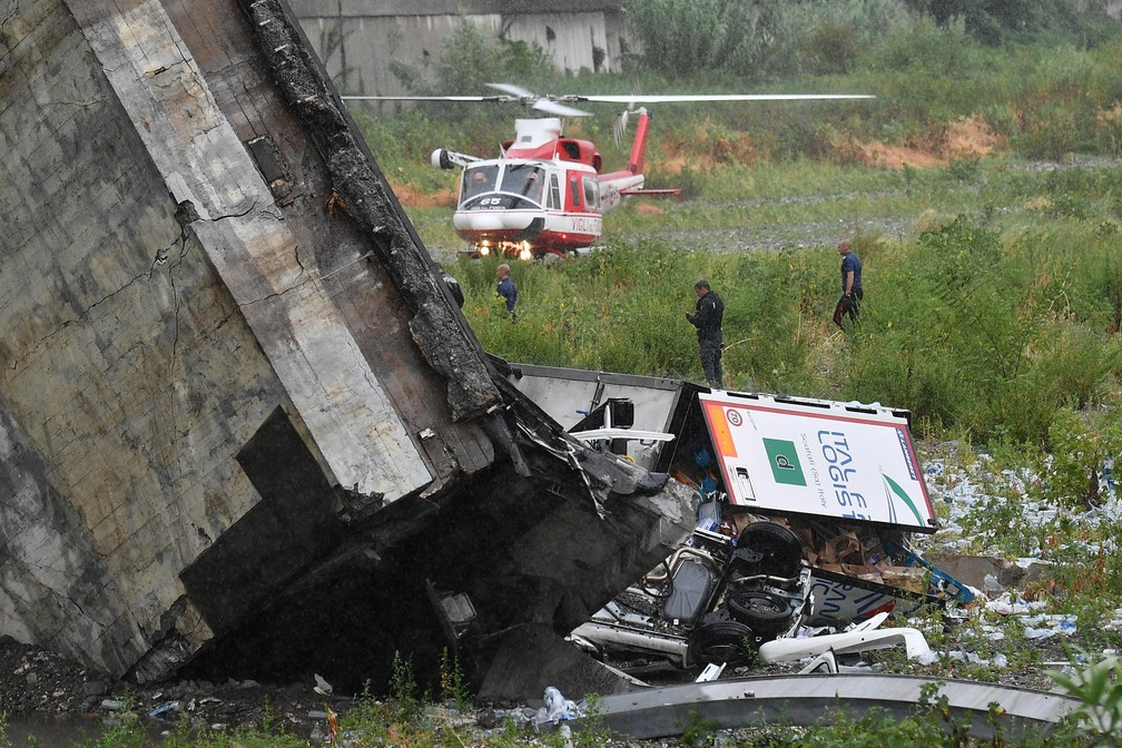 Bombeiros trabalham em escombros de parte de viaduto que desabou nesta terça-feira (14) em Gênova, na Itália (Foto: Luca Zennaro/ANSA via AP)
