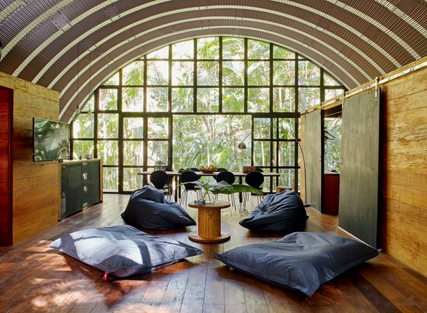 Living | O espaço de convivência tem uma visão ampla da mata através dos vidros, de 85 x 85 cm, na esquadria de alumínio, que chega a medir mais 5 m na parte mais alta da semiabóboda (Foto: Victor Affaro)