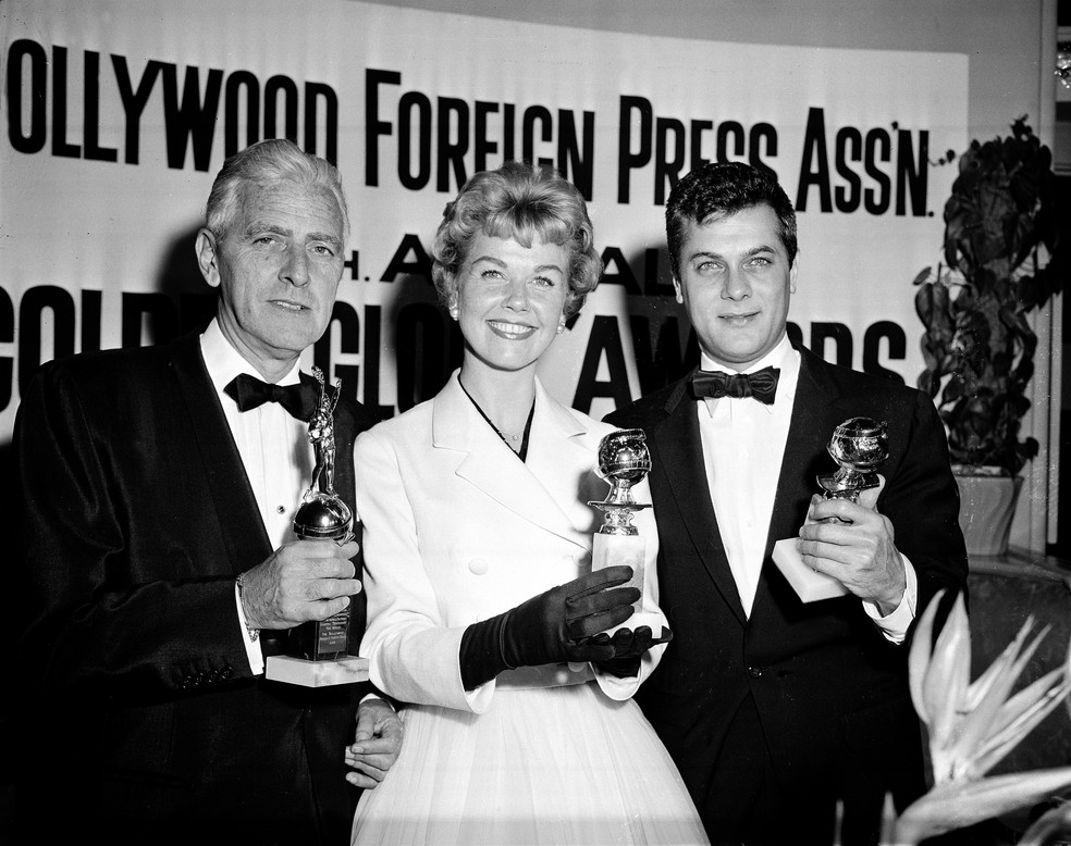 Doris Day posa ao lado de Buddy Adler (esquerda) e Tony Curtis (direita) com seus prêmios apresentados pela Hollywood Foreign Press Association em 1958 — Foto: Associated Press