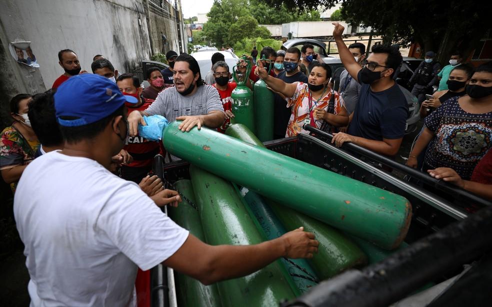 Parentes de pacientes hospitalizados se reúnem para comprar oxigênio e encher botijões em empresa privada em Manau — Foto: REUTERS/Bruno Kelly