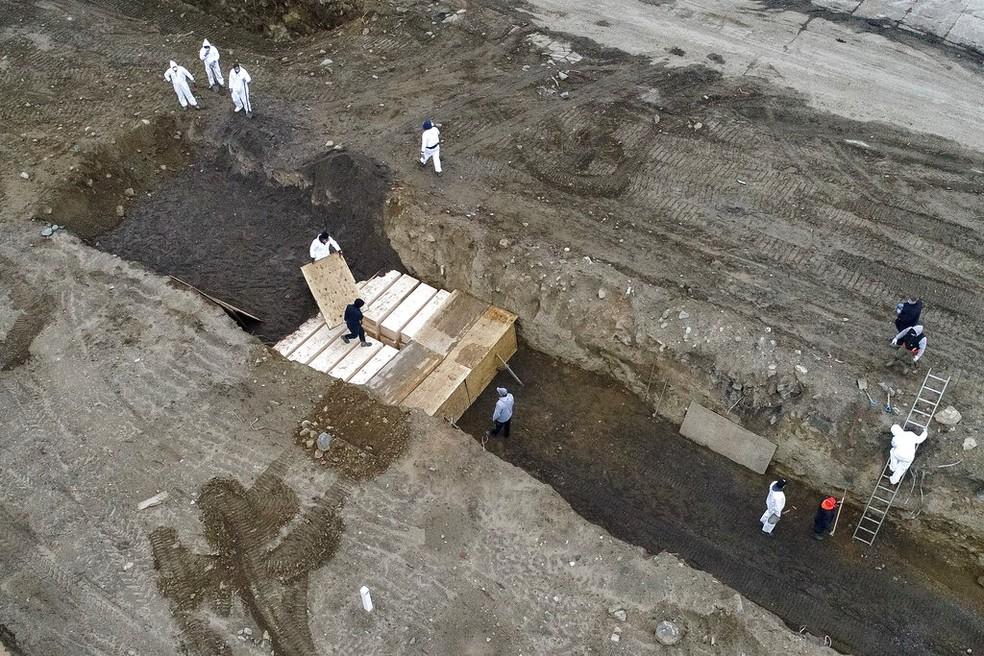 Vítimas de Covid-19 são enterradas em vala comum em Nova York — Foto: AP Photo/John Minchillo