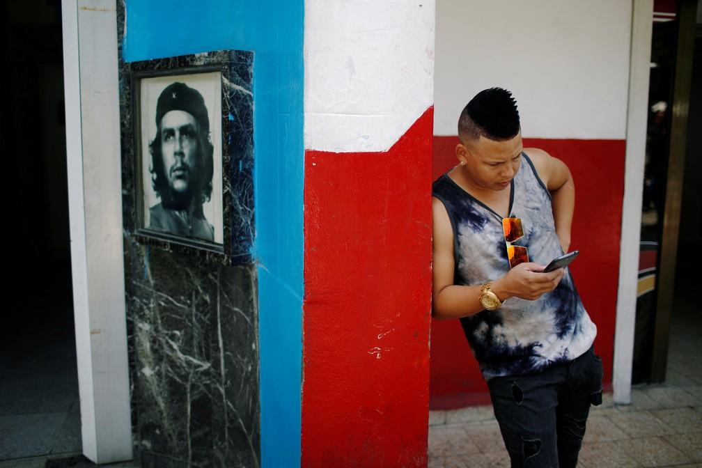 Jovem verifica celular em Cuba perto de um hotspot de internet  — Foto: Tomas Bravo/Reuters