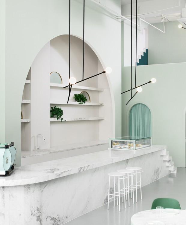 O minimalismo está nas paredes altes, nos lustres delicados e no mármore do balcão  (Foto: James Morgan/ Reprodução)