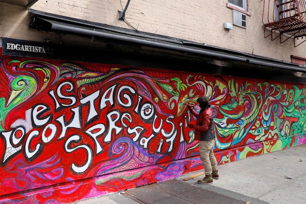 22 de março - O artista e designer Edgartista dá retoques no seu mural que diz: 'O amor é conagiante. Espalhe-o', durante quarentena devida ao coronavírus, no Brooklyn, em Nova York — Foto: Andrew Kelly/Reuters