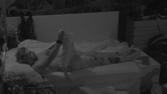 Alan senta na cama e veste casaco no Quarto Ouro