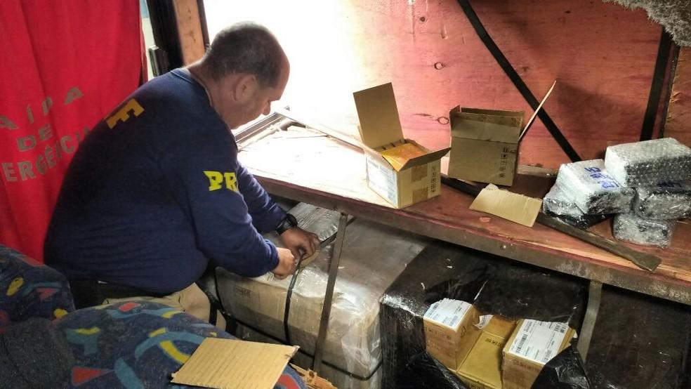 Momento em que policiais acessavam fundo falso recheado de mercadorias (Foto: PRF/Divulgação)