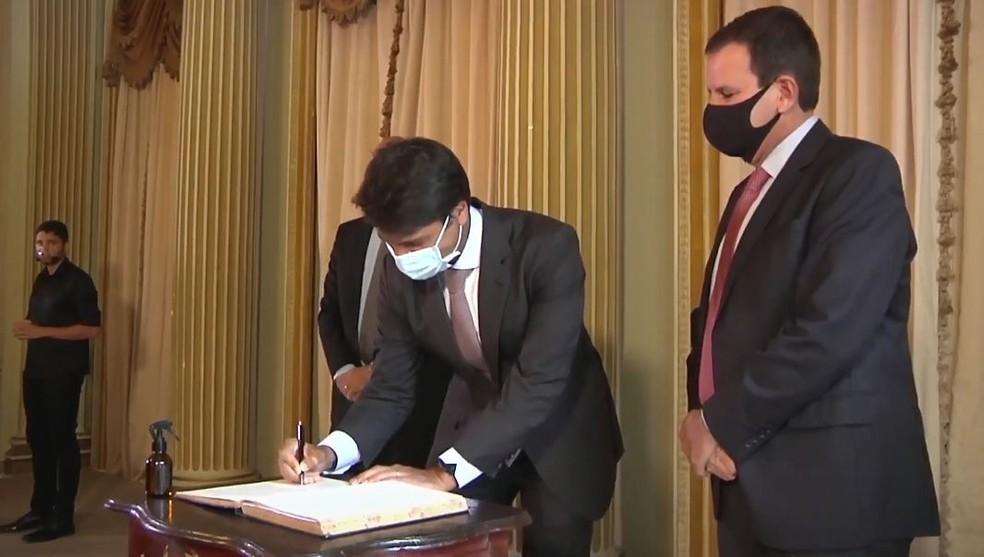 Novo secretário de Fazenda, Pedro Paulo assina o livro durante cerimônia de posse, observado por Paes — Foto: Reprodução