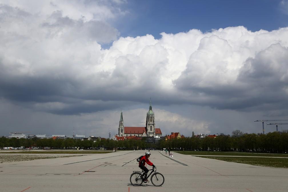 Ciclista atravessa a área onde é realizada a Oktoberfest em Munique, em frente à igreja de St. Pauls, na Alemanha — Foto: Matthias Schrader/AP