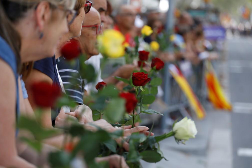 Manifestantes seguram rosas antes da marcha prevista para a tarde deste sábado no centro de Barcelona (Foto: Juan Medina/Reuters)