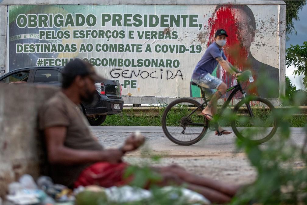 Foto mostra outdoor com texto 'obrigado presidente, pelos esforços e verbas destinadas ao combate a Covid-19 #fechadoscombolsonaro' ao lado do rosto do presidente Jair Bolsonaro coberto de tinta vermelha e pichado com a palavra 'genocida' em Carpina (PE), na Zona da Mata Norte pernambucana, a 45 km de Recife. — Foto: Leo Malafaia/AFP
