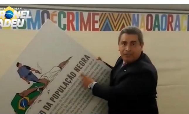 O deputado federal Coronel Tadeu (PSL-SP) quebra cartaz de exposição da Câmara contra racismo