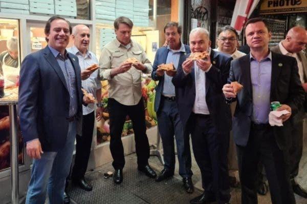 O presidente Jair Bolsonaro come pizza ao lado de seus auxiliares em pizzaria em Nova York