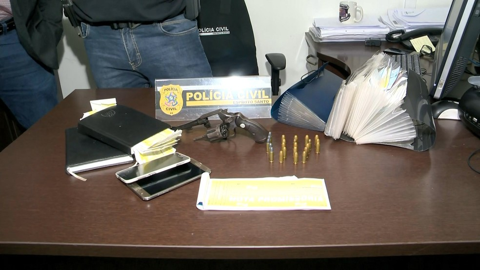 Entre o material apreendido estavam um revólver e uma pasta com cheques e promissórias — Foto: Reprodução/TV Gazeta