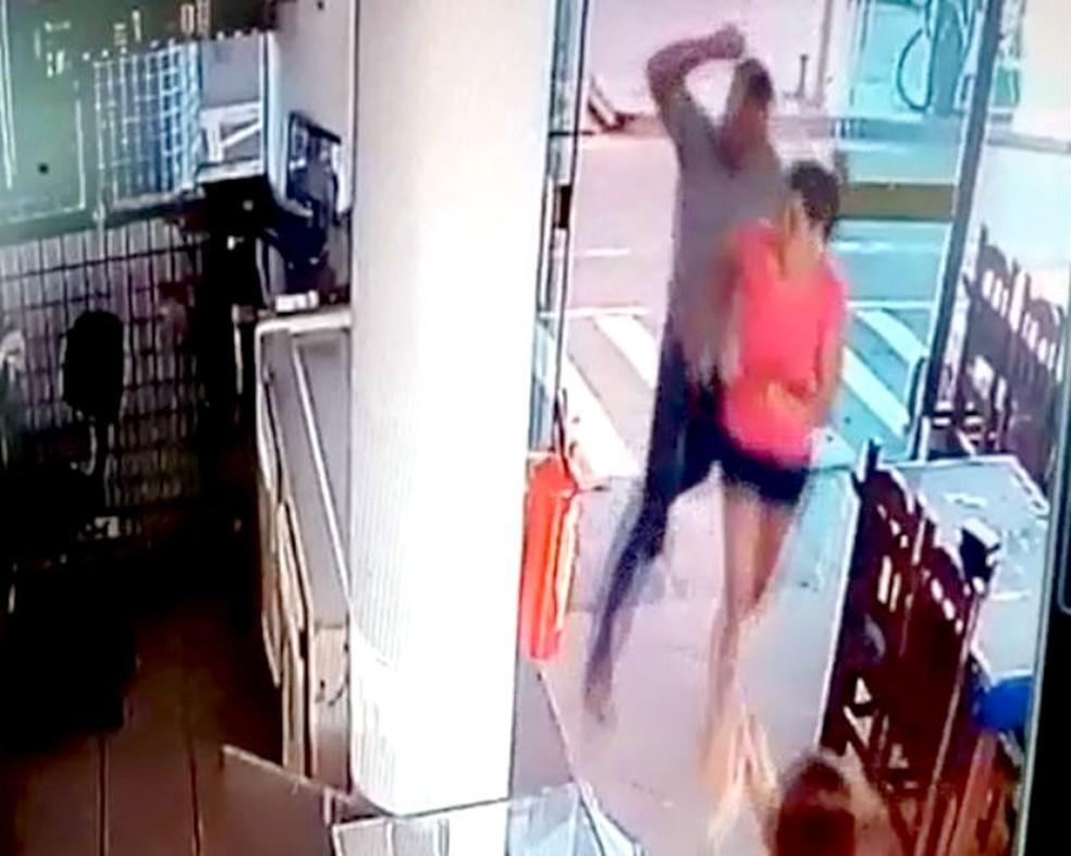 Após escapar dos disparos, irmão do genro da mulher a acerta com um soco na cabeça — Foto: Câmeras de segurança/Reprodução