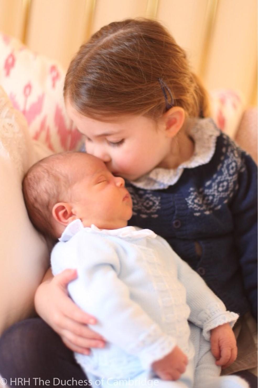 Princesa Charlotte segura o irmão mais novo, o príncipe Louis (Foto: Reprodução/Twitter)