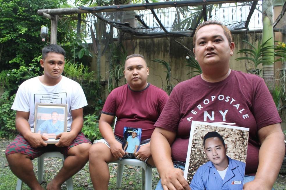 Os irmãos Rocky, Mike e Lorenzo posam para fotos enquanto seguram um retrato de seu irmão Cherokee Capajo em casa em Dingle, província de Iloilo, centro das Filipinas — Foto: AFP