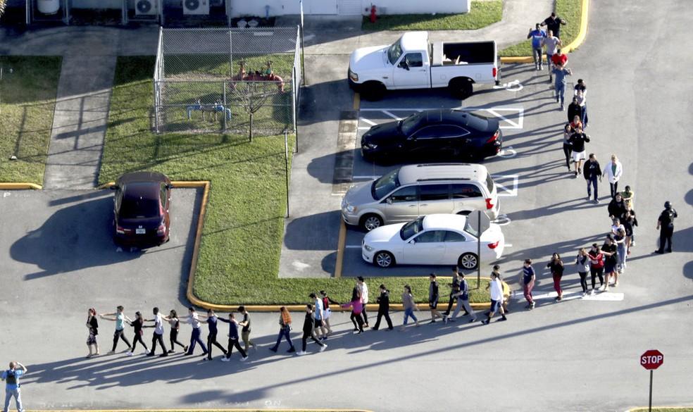 Os estudantes da Marjory Stoneman Douglas High School, na Flórida, são retirados em fila do prédio da escola depois que um tiroteio deixou mortos e feridos; a polícia afirmou que o atirador é um estudante de 19 anos que havia sido expulso da escola (Foto: Mike Stocker/South Florida Sun-Sentinel via AP)