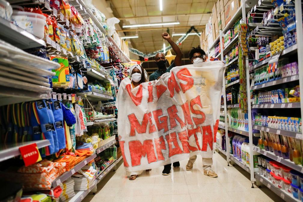 Manifestantes carregam faixa com os dizeres 'Vidas Negras Importam' dentro de unidade do Carrefour em Brasília, nesta sexta-feira (20).  — Foto: REUTERS/Adriano Machado