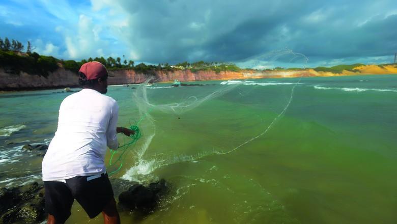 Pescador joga a tarrafa para captura de sardinhas na Praia de Tabatinga, em Nísia Floresta (RN) (Foto: Léo Caldas)