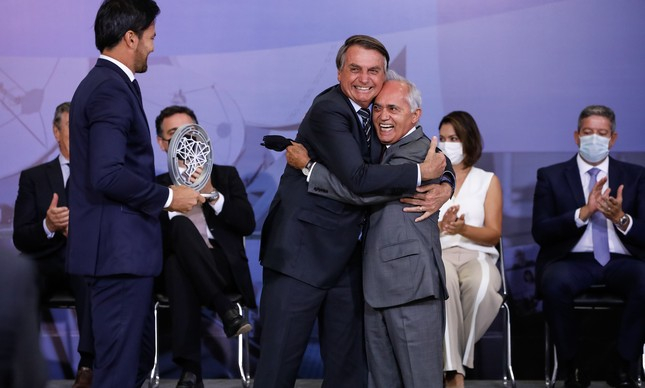 """Bolsonaro abraça Carreiro em solenidade que premiou """"contribuição à comunicação"""": antes da embaixada em Portugal, relatório favorável ao projeto de 5G do governo"""