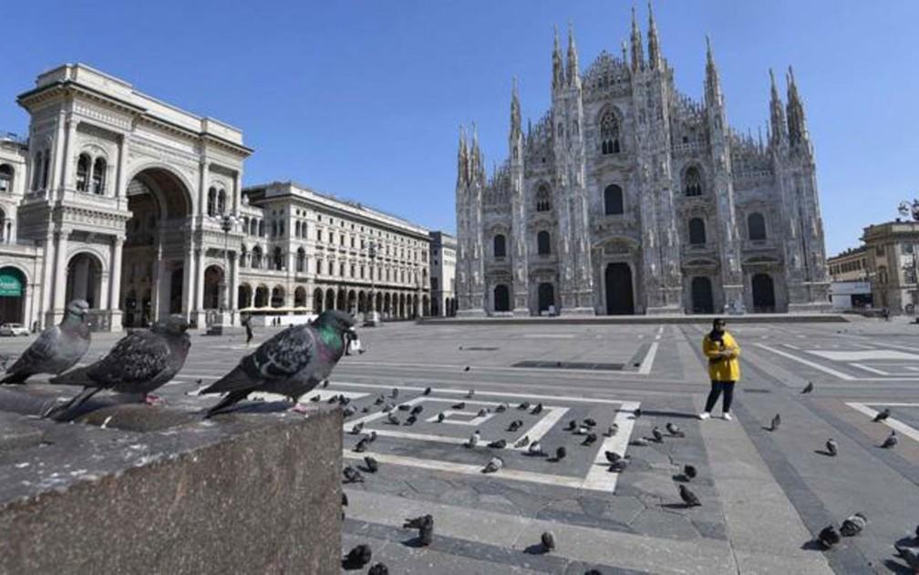 A Praça Duomo, em Milão, está deserta. Em toda a Itália, o governo determinou medidas de restrição da circulação de pessoas e ordenou o fechamento de estabelecimentos comerciais, exceto mercados e farmácias  — Foto: Daniel Dal Zennaro/EPA/BBC