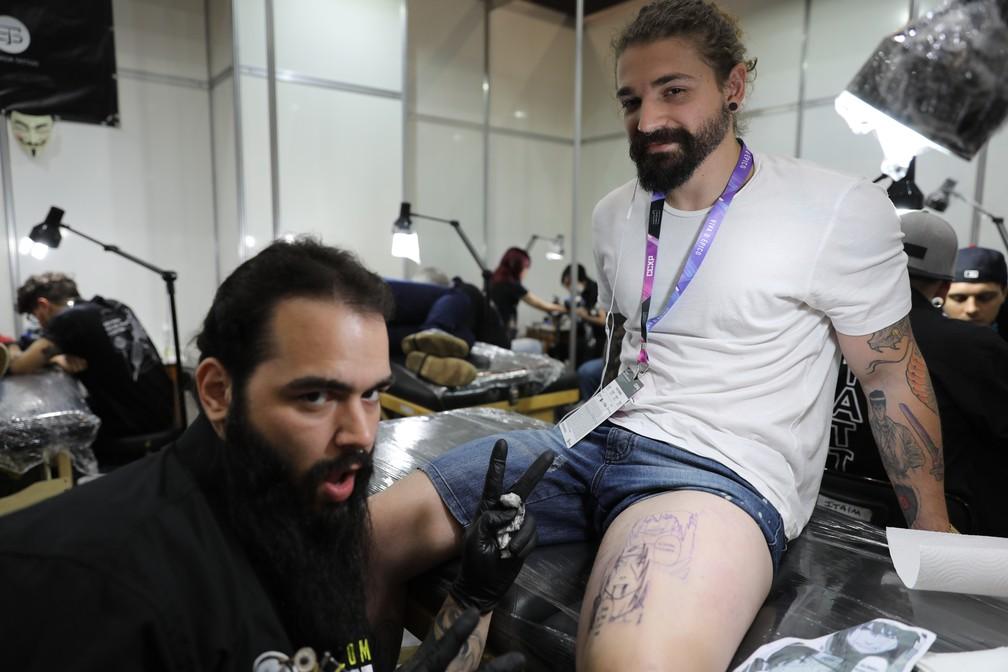 Ink Mali tatua uma cena de 'Naruto' com Itachi e Sasuke no marqueteiro Artur da Matta, de 29 anos, na CCXP 2018 — Foto: Fábio Tito/G1