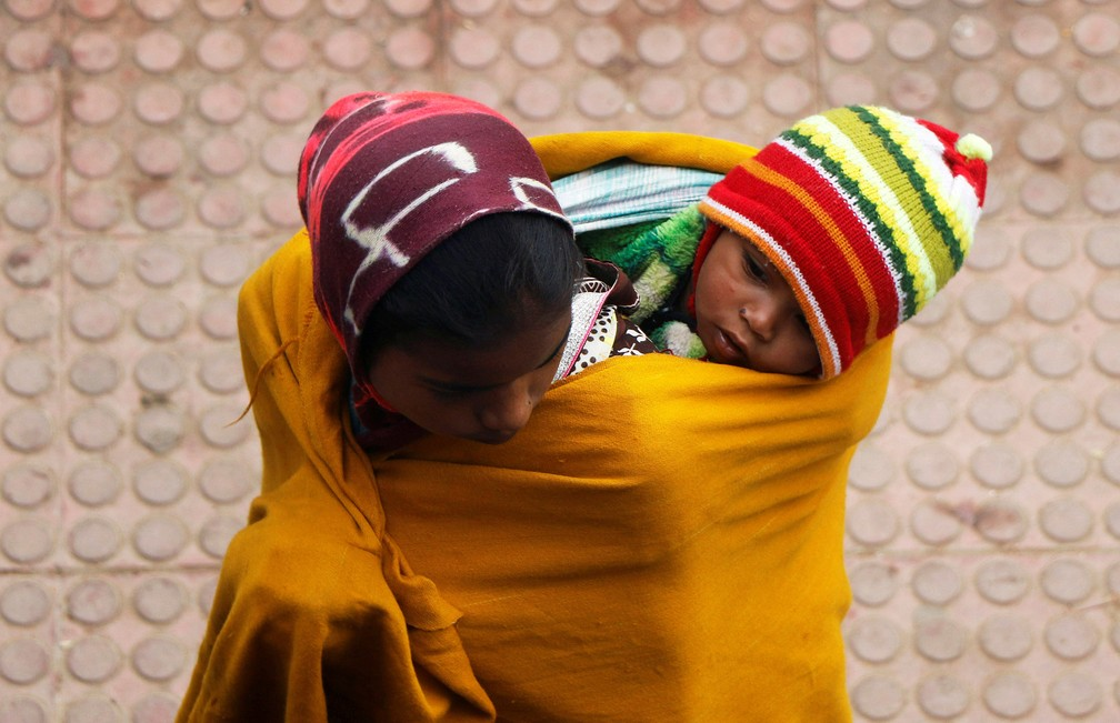 6 de janeiro - Mulher envolve criança em um xale enquanto espera por um trem em Agartala, na Índia  (Foto: Jayanta Dey/Reuters)