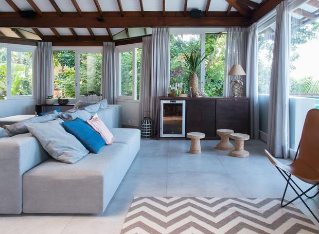 Com dupla face - uma voltada para a TV e a outra voltada para a varanda, o sofá tem sempre uma bela vista à frente (Foto: Cacá Bratke/Divulgação | Produção Deborah Apsan)