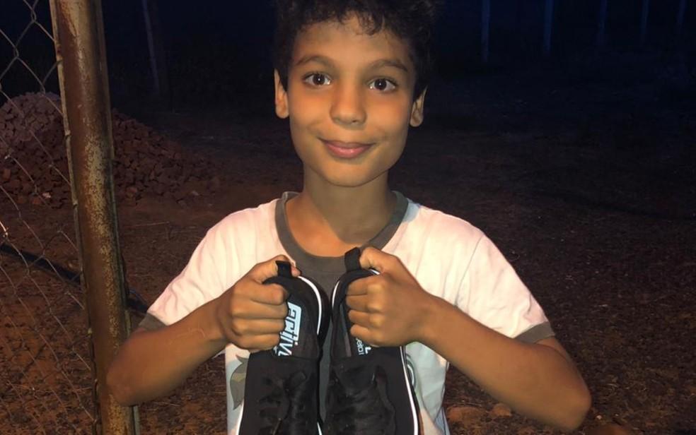 João Gabriel com o par de tênis que ganhou do dono da farmácia, em Caldas Novas — Foto: Arquivo Pessoal/Rafael Carneiro