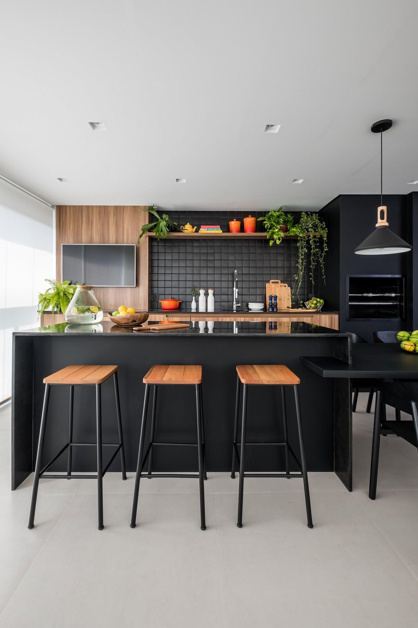 Bancada de granito preta com bancos e movéis de madeira e acessórios de área gourmet.